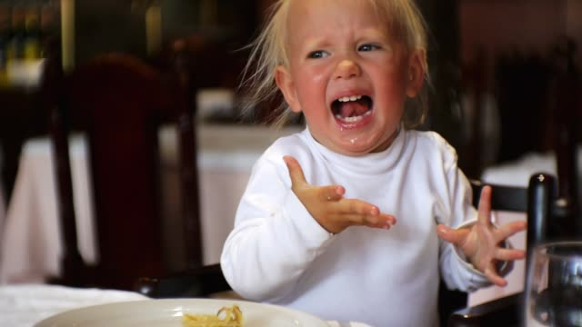 Baby eating food in restaurant. Caucasian blue-eyed child in highchair eats too spicy food and screams with surprise, opening the mouth.