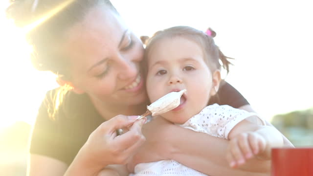 baby eating ice cream on a stick for a first time baby eating ice cream on a stick for a first time feeding stock videos & royalty-free footage