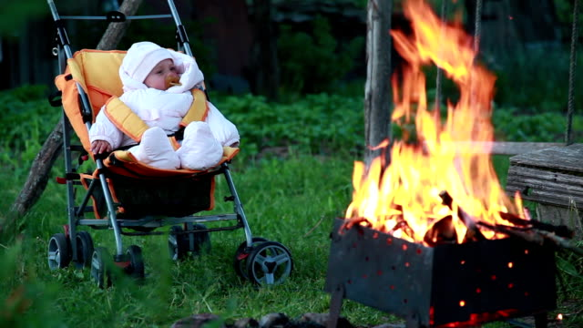 Baby falling asleep in front of the campfire video