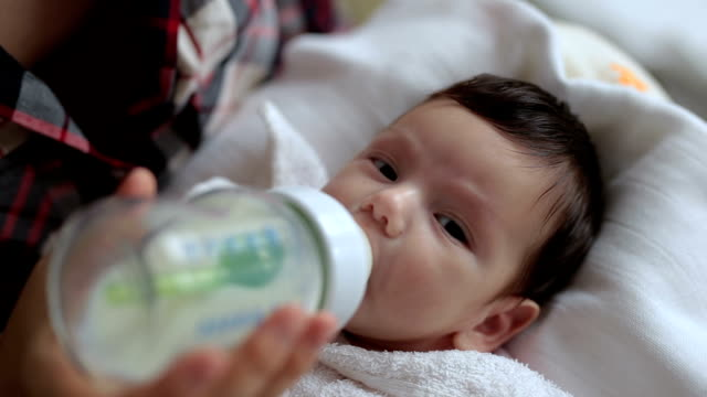 Baby fed by the mother 2 month old baby drinking from a baby bottle, held and fed by her mother. feeding stock videos & royalty-free footage