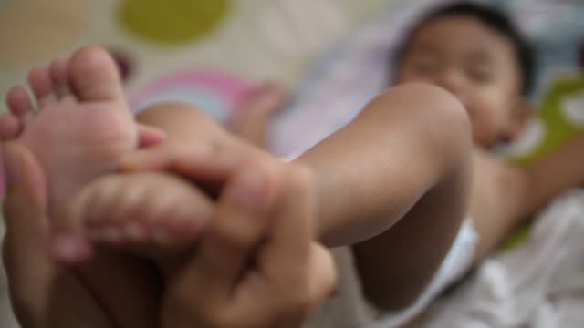 baby feet in mother hands - dito del piede video stock e b–roll