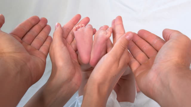 Baby feet in mothers and fsther hands. Happy Family concept. Closeup.