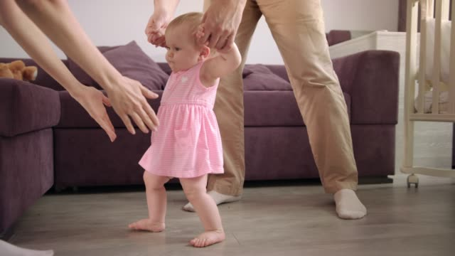 Baby first steps. Baby learning to walk. Family support little kid video