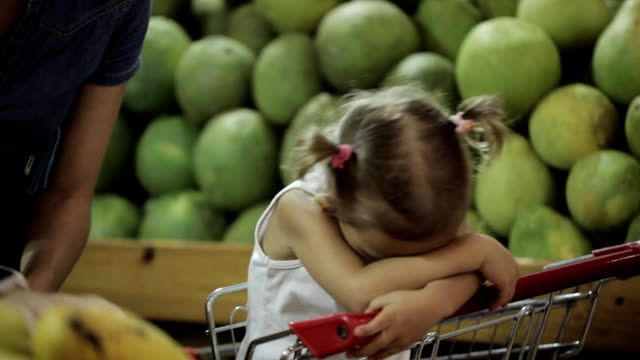 Baby get tired sit in shopping cart when her mom selecting fruits in supermarket video