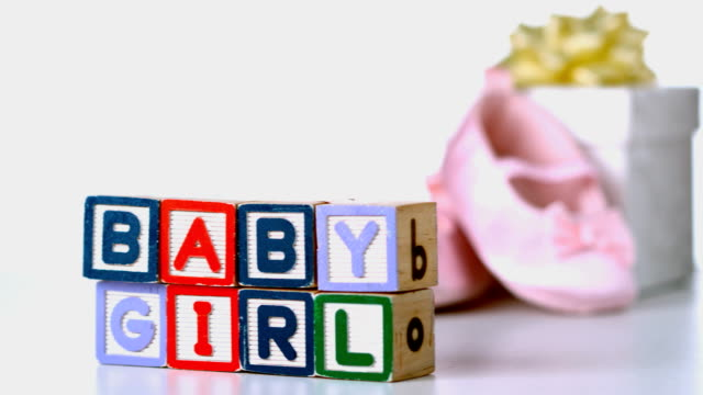 Baby girl blocks sliding across Baby girl blocks sliding across with booties and gift box in background in slow motion baby booties stock videos & royalty-free footage