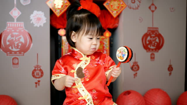 vidéos et rushes de bébé fille célébrant le nouvel an chinois à la maison - nouvel an chinois