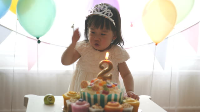 baby girl celebrating her second birthday at home Asian baby girl celebrating her second birthday at home happy birthday stock videos & royalty-free footage