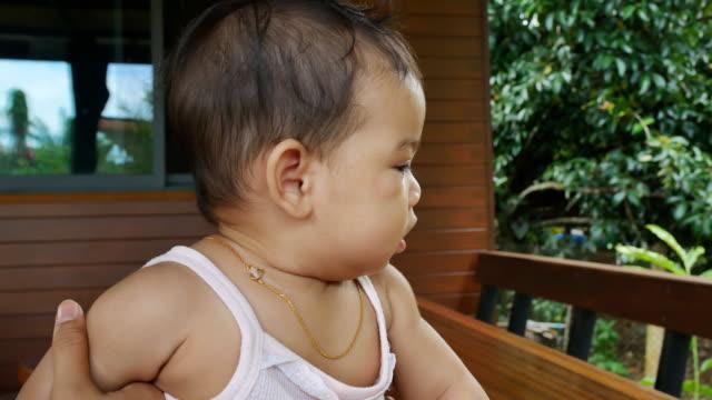 baby girl chewing toy - abbigliamento da neonato video stock e b–roll