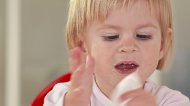 stockvideo's en b-roll-footage met hd: baby girl cleaning her face after eating - background baby