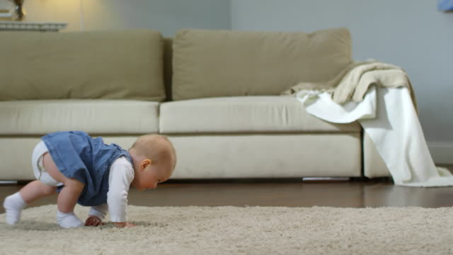 Baby Girl Crawling and Falling Over Full shot of adorable Caucasian baby girl crawling on all fours on carpet in living room at home, trying to stand up but falling on her back, then rolling over to crawl again crawling stock videos & royalty-free footage
