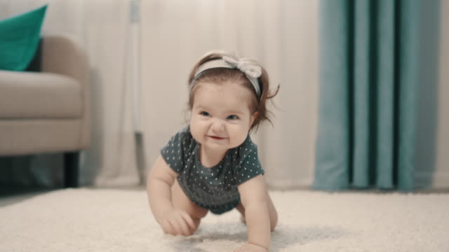 baby girl crawling on all fours on floor at home - moquette video stock e b–roll