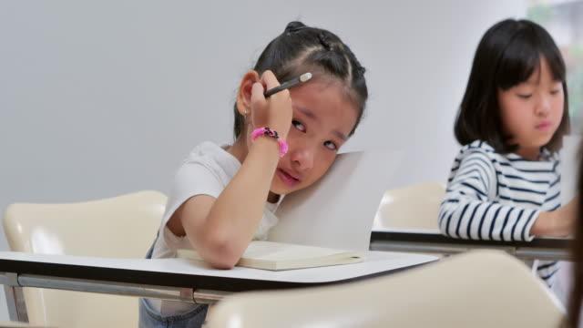 울고 있는 아기 소녀. 교실에서 노트북을 쓰는 초등학생. 여자 학습 수업, 귀여운 소녀는 그녀의 숙제를 만드는, 테이블에 여학생 스터드.아이들의 교육, 다시 학교에 - 짜증 스톡 비디오 및 b-롤 화면