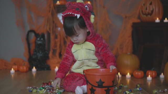 baby girl dressed up playing at halloween party - halloween candy стоковые видео и кадры b-roll