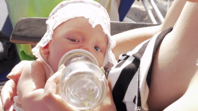 Baby girl drinking water from bottle outdoor