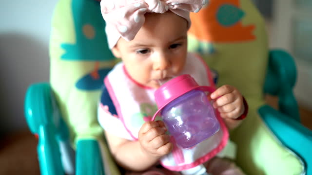 Baby girl drinking water in a high chair Baby girl drinking water in a high chair charming stock videos & royalty-free footage