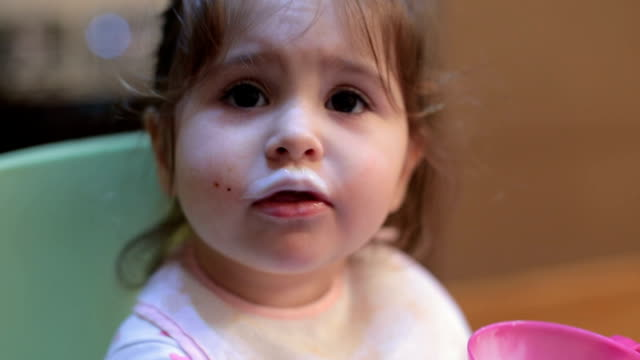 baby girl drinking yogurt on her own - baffo peluria del viso video stock e b–roll