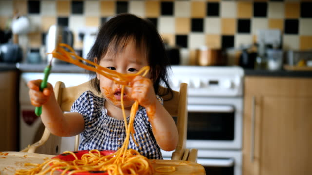 baby girl eating messy spaghetti baby girl eating messy spaghetti at home kitchen spaghetti stock videos & royalty-free footage