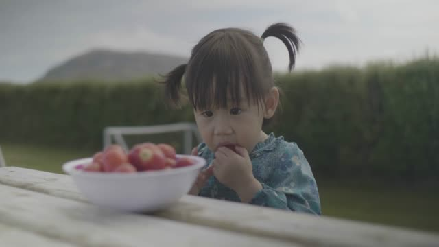 baby girl eating strawberry