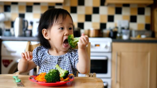 baby girl eating vegetable - broccolo video stock e b–roll