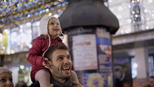 baby girl enjoying christmas lights on dad's back - happy holidays filmów i materiałów b-roll