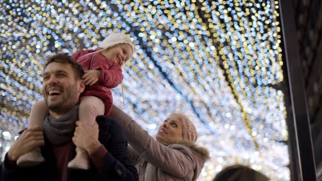 babymädchen genießen weihnachten lichter auf papas rücken - weihnachtsmarkt stock-videos und b-roll-filmmaterial