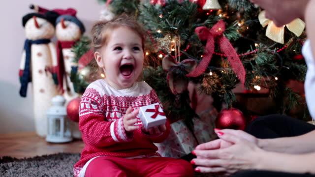 baby flicka blir närvarande för nyår semester - christmas present bildbanksvideor och videomaterial från bakom kulisserna