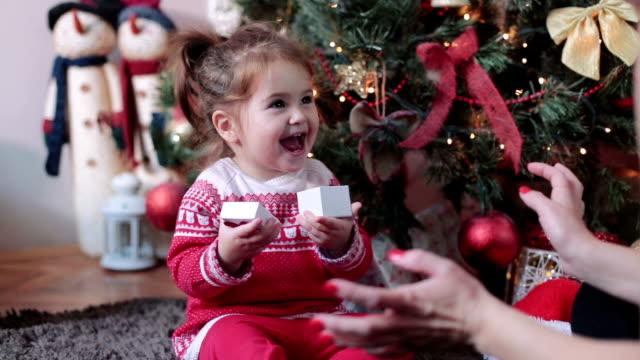 baby flicka blir närvarande på jul - christmas gift family bildbanksvideor och videomaterial från bakom kulisserna