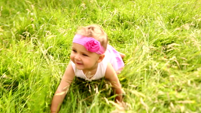 Baby girl having fun discovering and crawling in nature video