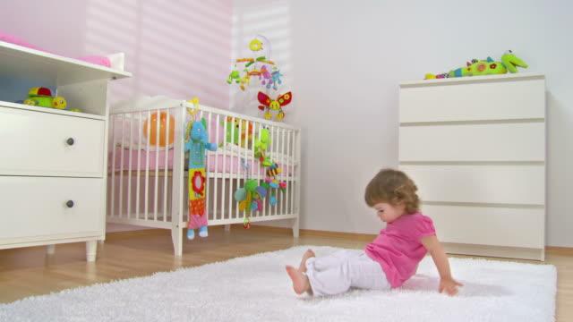 stockvideo's en b-roll-footage met hd crane: baby girl having fun on the carpet - background baby