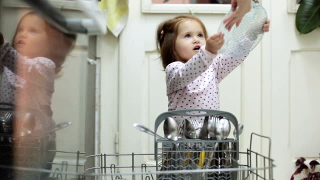 baby girl helping her mother with dishes Giving her mother dishes from Disher machine Daughter is assisting her mother in the kitchen dishwasher stock videos & royalty-free footage