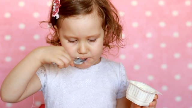 Baby girl is eating a yogurt for breakfast. The child eats cottage cheese video