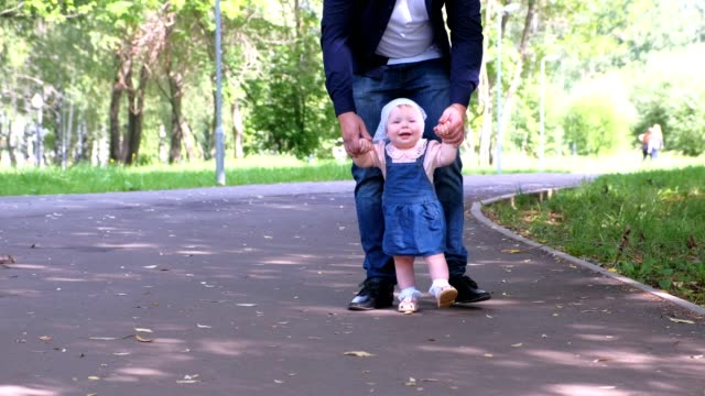 Baby girl is trying to go making first steps holding dad's hands in city park. video