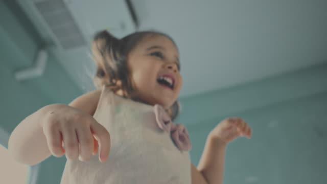 vídeos de stock e filmes b-roll de baby girl jumping on bed, slow motion - criança pequena