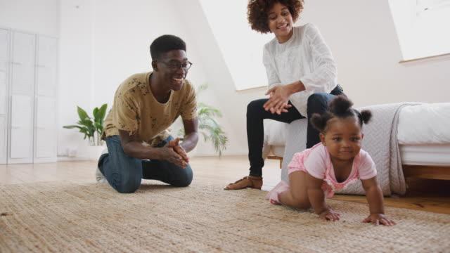 vidéos et rushes de bébé apprenant à ramper à la maison pendant que les parents s'asseyent sur l'étage et donnent l'encouragement - ramper