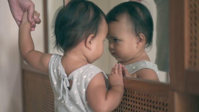 vídeos de stock e filmes b-roll de baby girl looking at herself on mirror - espelho
