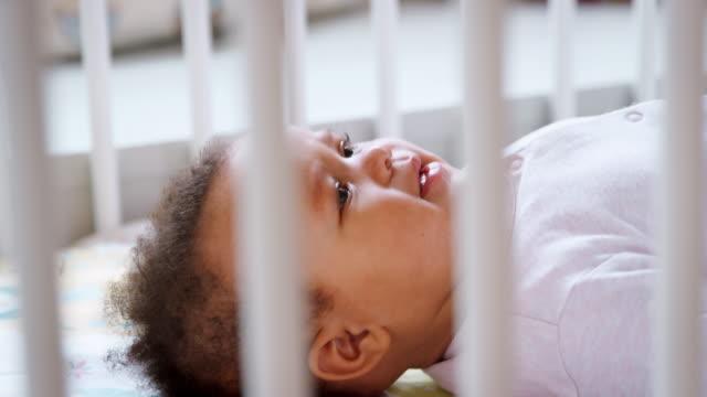 vídeos de stock, filmes e b-roll de bebê menina deitada nas costas no berço berçário e sorrindo - consciência negra