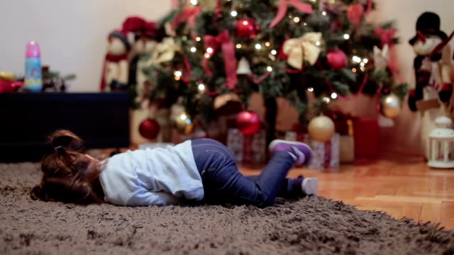 baby girl lying on the floor in front of christmas tree and sulking , she is tired video
