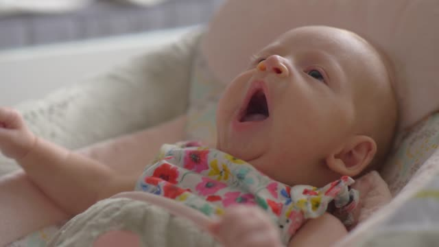Baby girl of two months lying in bouncy seat and yawning Close-up shot of two months baby girl yawning and looking around lying in comfortable bouncy seat at home rocking chair stock videos & royalty-free footage