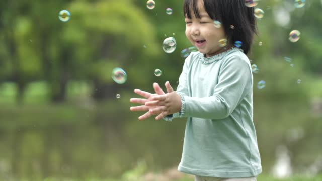 Baby girl play bubbles at spring garden Baby girl play bubbles at spring garden childhood stock videos & royalty-free footage