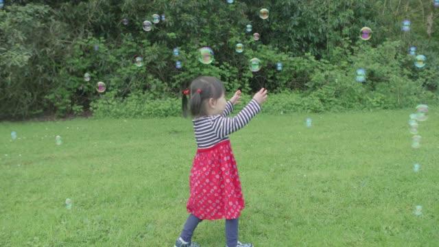 stockvideo's en b-roll-footage met meisje van de baby spelen bubbels op de lentetuin - kindertijd