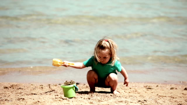 Baby girl playing bucket and shovel dig on sand beach sea video