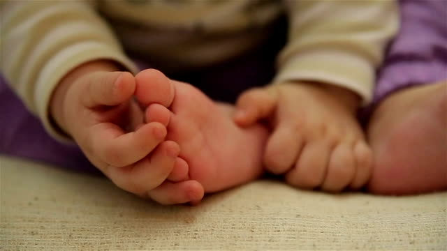 Babymädchen spielen mit ihren Füßen – Video