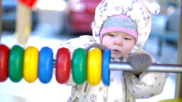 Baby girl playing with abacus in courtyard video