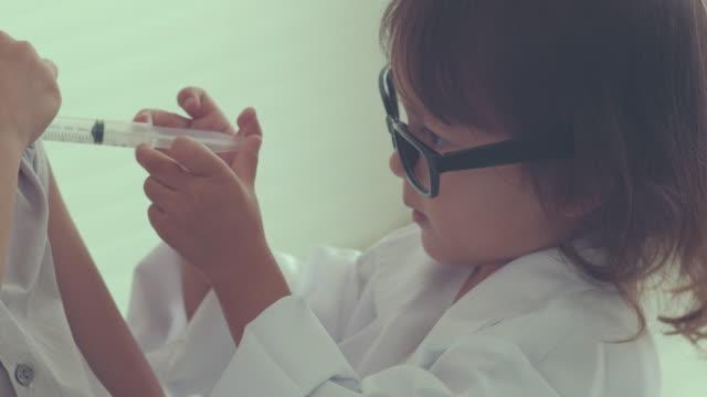 vídeos y material grabado en eventos de stock de niña fingir jugar al doctor - flu shot