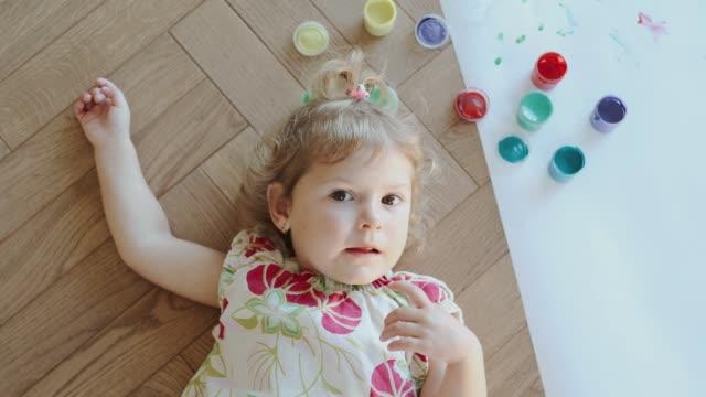 baby girl resting on the floor. - matita colorata video stock e b–roll
