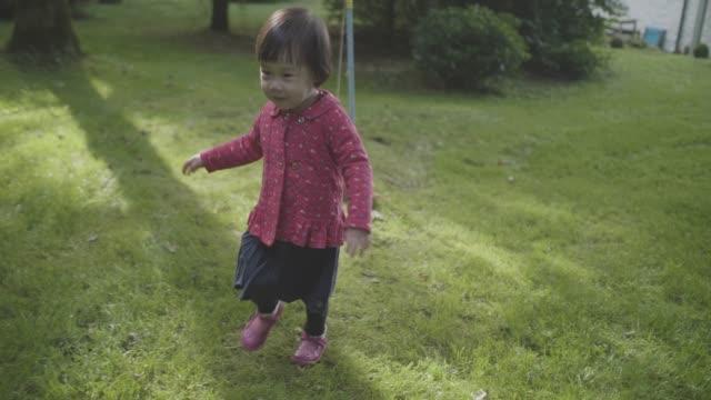 baby girl running at spring home garden