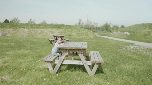 vídeos de stock e filmes b-roll de baby girl sitting on picnic table - mesa mobília