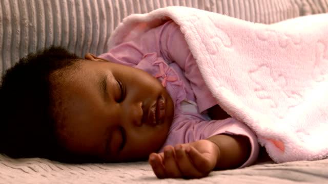 baby girl sleeping on the sofa - baby sleeping bildbanksvideor och videomaterial från bakom kulisserna