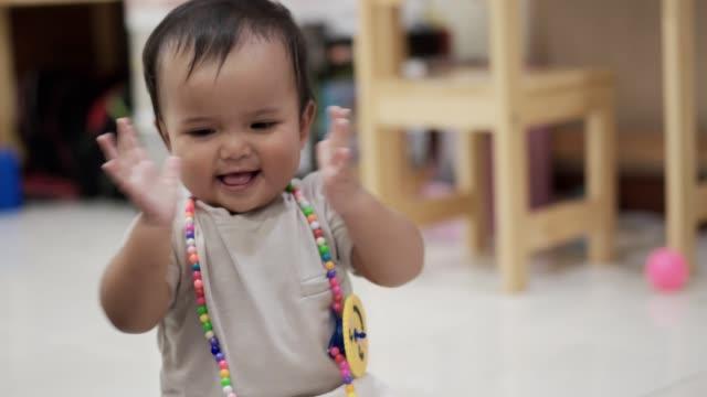 vídeos de stock e filmes b-roll de baby girl smiling and clapping hands - criança pequena
