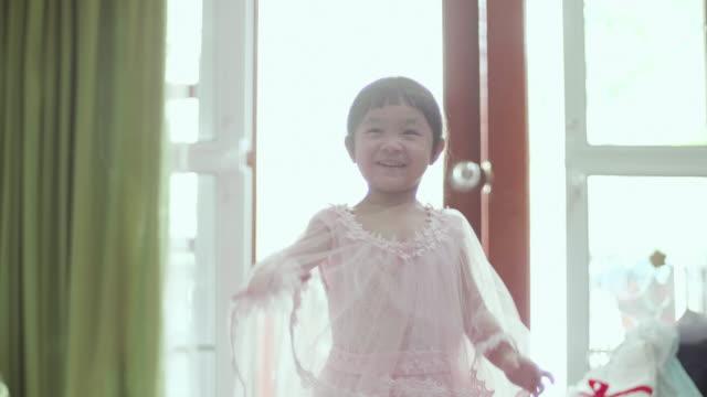 babymädchen versucht, auf ein neues kleid - neues zuhause stock-videos und b-roll-filmmaterial